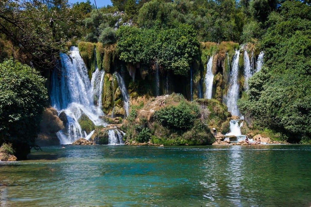 Waterfalls in a green lake at Kravice Falls