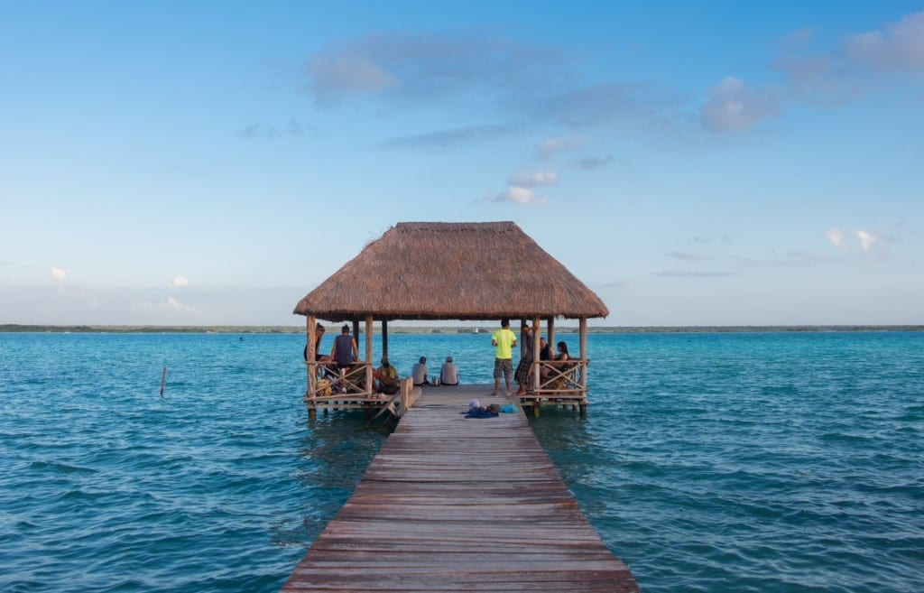 A dock leading to a sitting area with a thatched roof, on Bacalar Lake.
