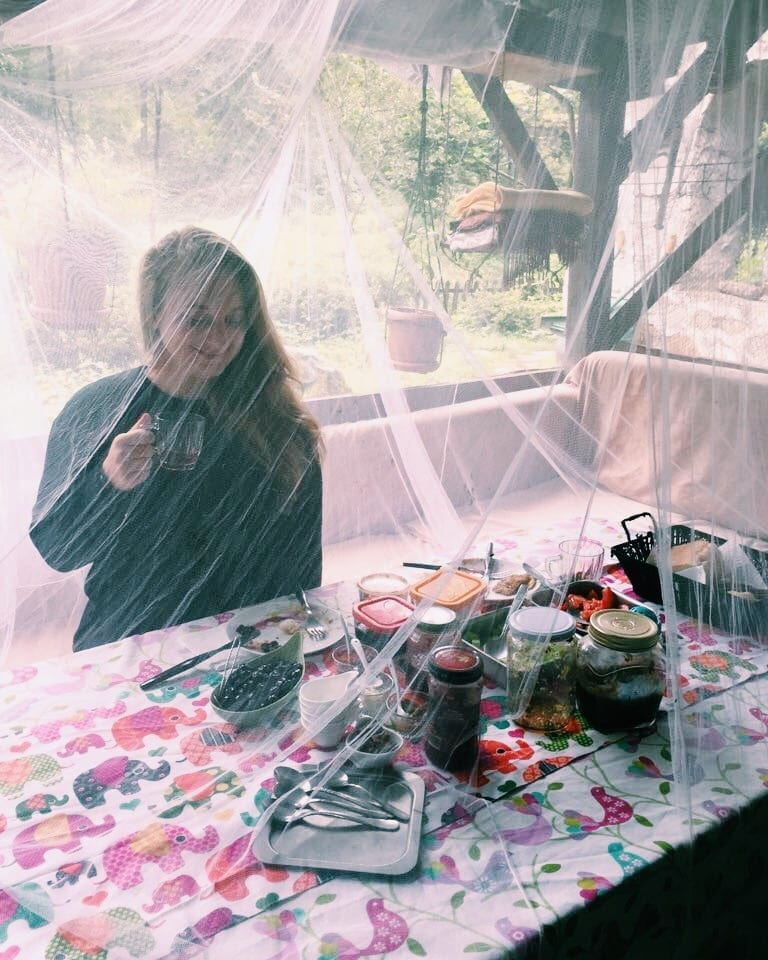 Katie sitting down to a meal underneath mosquito netting, smiling and drinking a cup of tea.