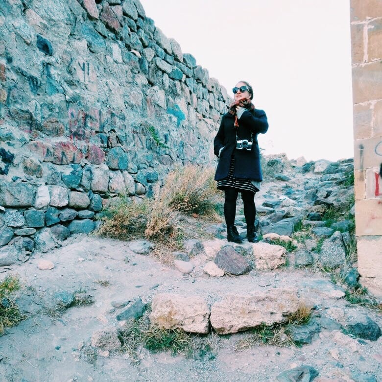 Katie bundled up in a coat and standing on a rocky path in Ani, Turkey.