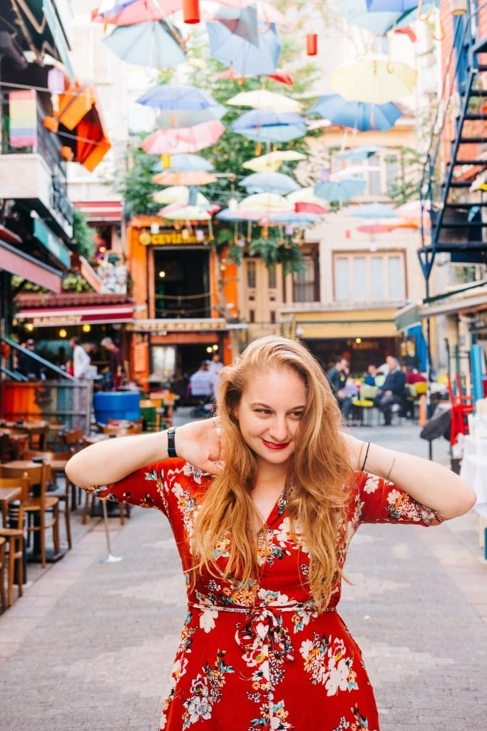 Katie wearing a red dress and smiling on an Istanbul street with bright shops and hanging umbrellas.