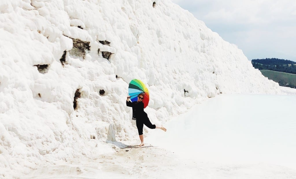 Katie dancing in the bright white travertine pools of Pamukkale, holding a rainbow-striped umbrella.