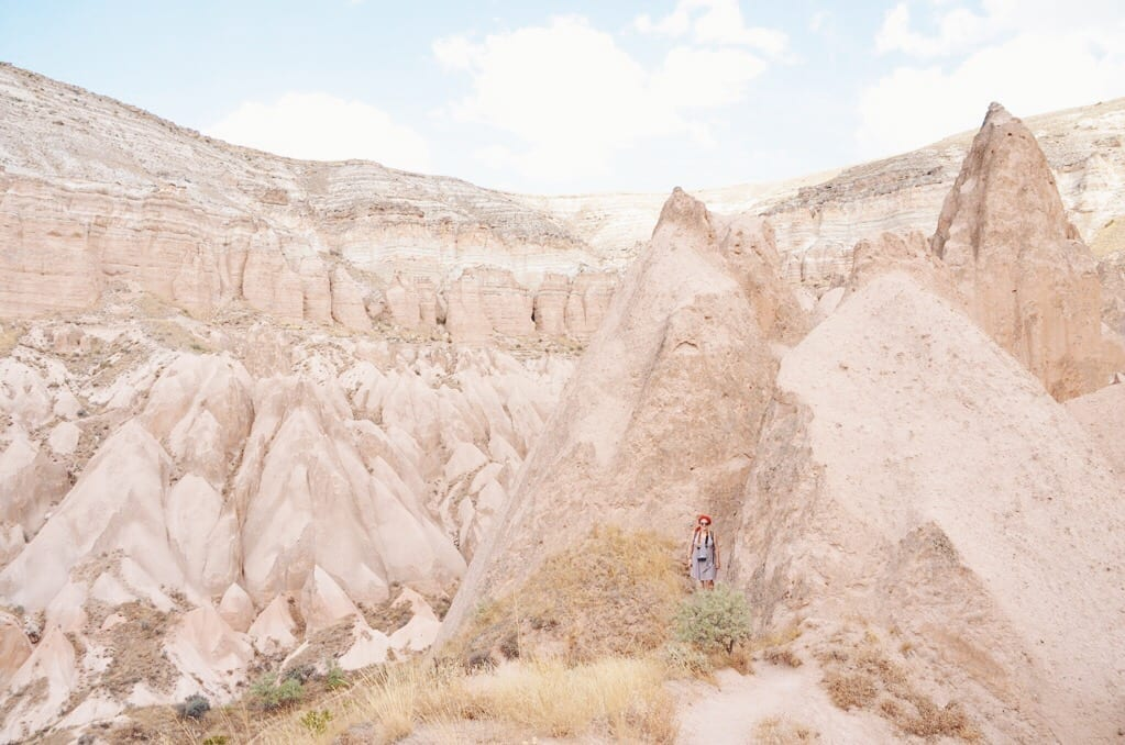 The giant triangle-shaped rocks of Cappadocia, with a tiny Katie next to one for scale.