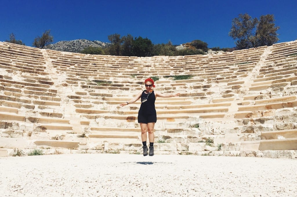Katie jumping for joy in front of a Roman amphitheater.