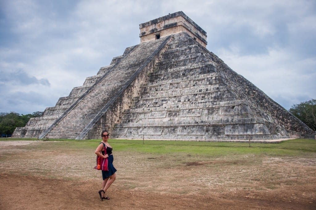 Kate standing in front of the gray stone pyramid of Chichen Itza in Mexico. The sky is cloudy and Kate miraculously has no other people in the photo.