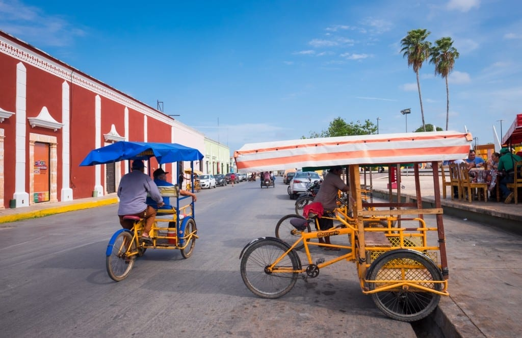 Two pushcarts in front of a red and white colonial building underneath. bright blue sky in Campeche.