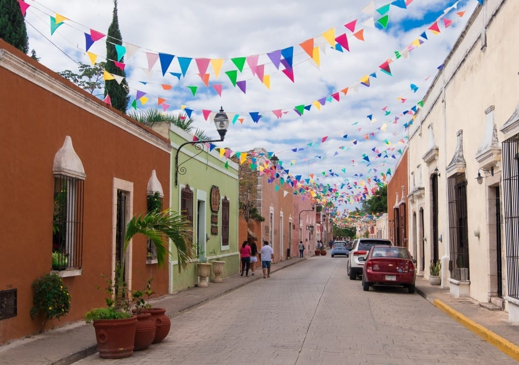 A street in Valladolid painted in bright colors, with multicolored triangular flags hanging between the buildings.