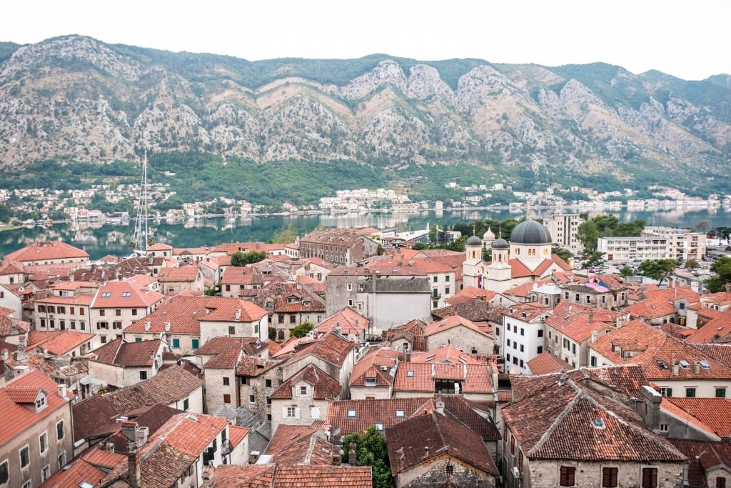 Orange roofs of Kotor against a gray-green mountain backdrop at dawn.