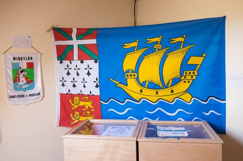 The St. Pierre and Miquelon flag with a yellow cartoon ship sailing on blue water.