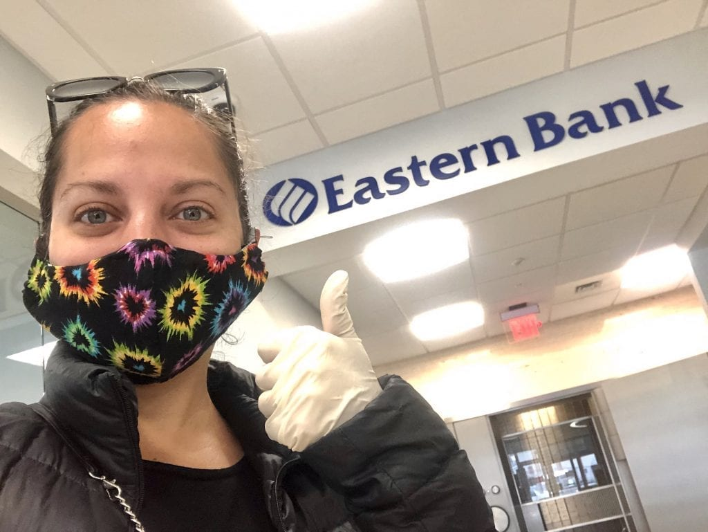 """Kate poses with a mask on by an """"Eastern Bank"""" sign, giving the thumbs up with a rubber gloved hand."""