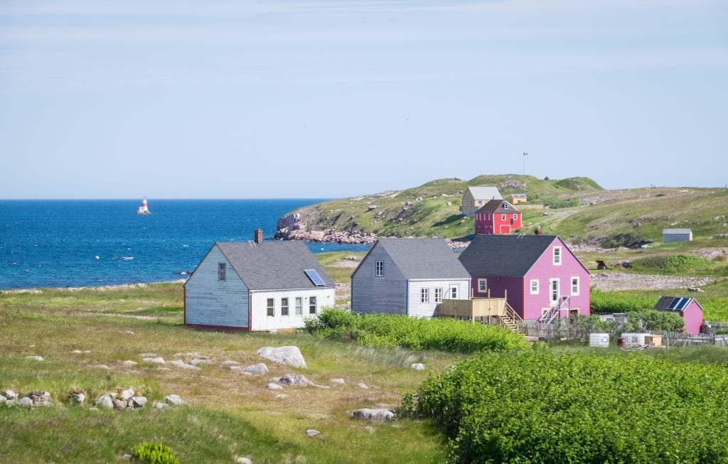 White, gray, and purple cottages overlooking the shoreline and a lighthouse in the distance.
