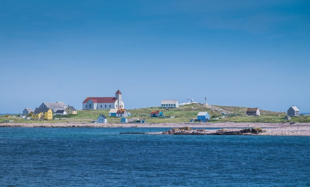 Il aux Marins, with a church and brightly colored houses on the edge of the rocky shoreline.