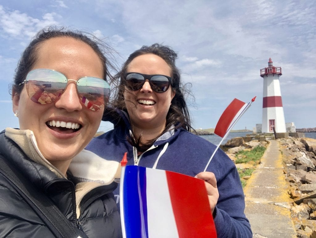 Kate and Cailin stand in front of the lighthouse of St. Pierre, waving mini French flags.
