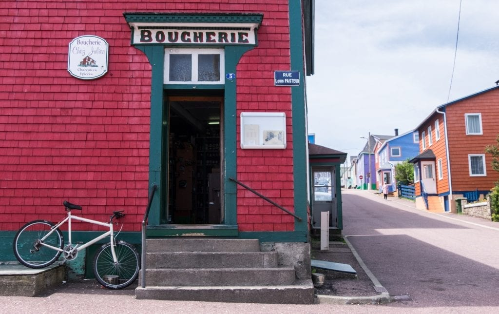 """A red shingled house with a doorway reading """"Boucherie"""" and a white bicycle parked next to it."""
