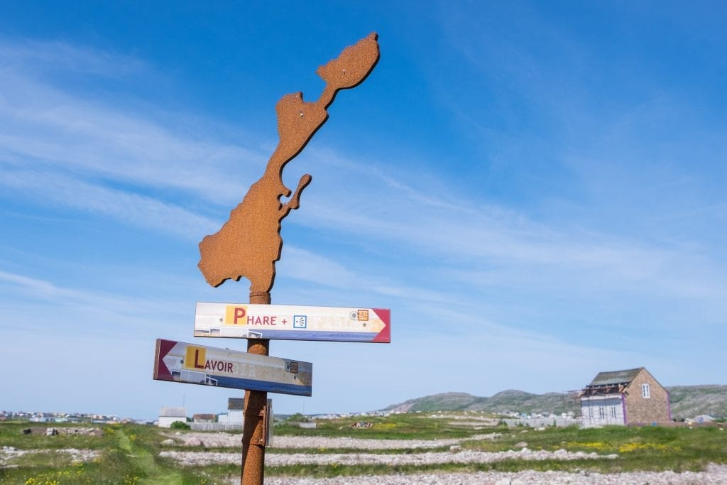"""An island-shaped sign against a blue sky with signs pointing to """"Phare"""" and """"Lavoir."""""""