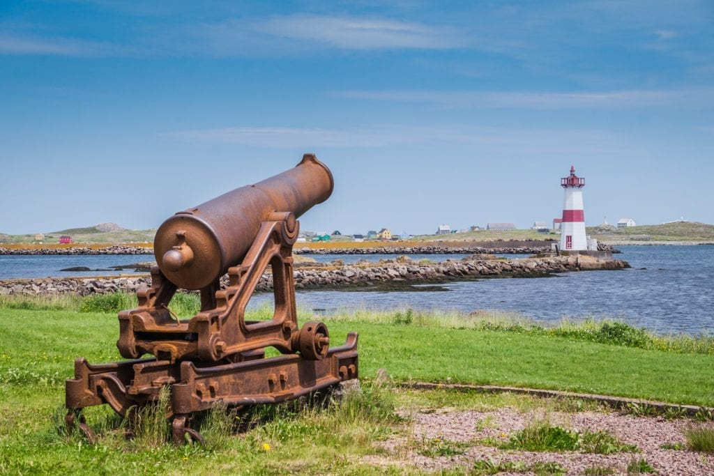 A rusty cannon in the foreground, pointing in the direction of a red and white lighthouse in the distance.