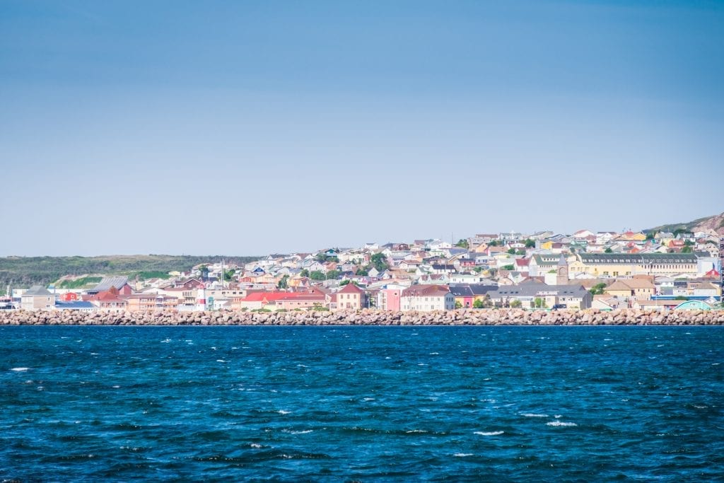 Colorful houses on the shore of St. Pierre, the bright blue ocean in front.