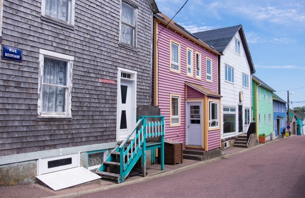 Weatherbeaten gray, purple, white, and green homes on a street in St. Pierre labeled Rue Boursaint.