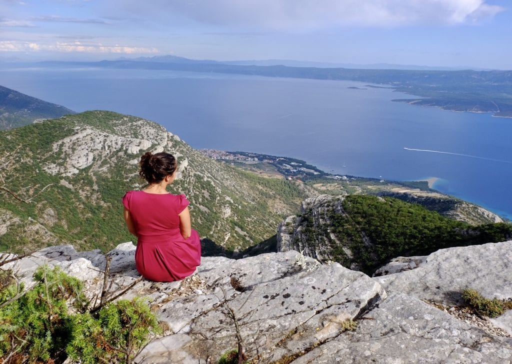 Kate wears a red dress and sits on the edge of a mountain overlooking the view to the sea in Brač, Croatia.