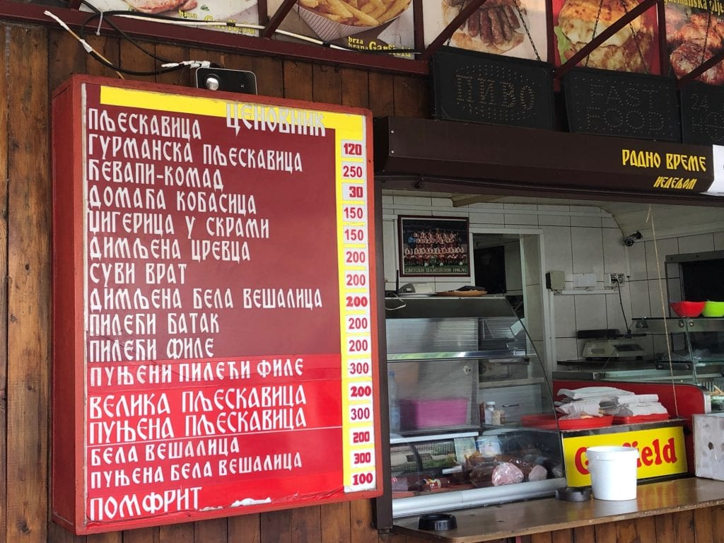 A counter at a takeaway grill with all the menu items written in Cyrillic.