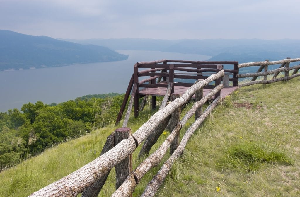A wooden fence and balcony overlooking the Danube river on a cloudy day.