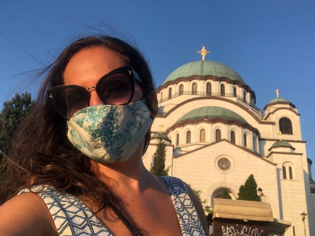 Kate wears a green and white dress and a green and white face mask with sunglasses, in front of the green and white church in Belgrade underneath a bright blue sky.