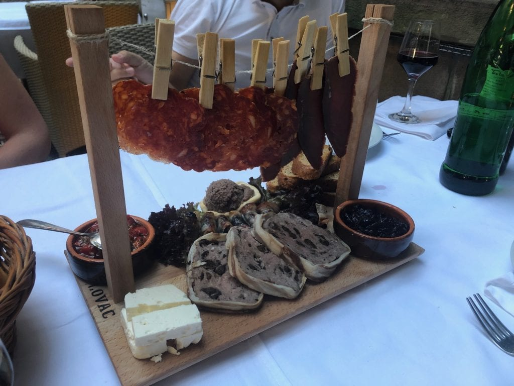 A platter of meats, complete with chorizo-like cured meats hanging from a clothesline on top!