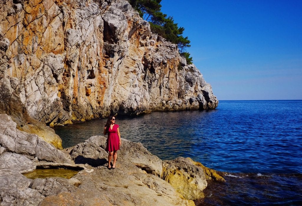 Kate wears a red dress and stands on a rocky slap leading into the bright blue ocean, stone cliffs topped with evergreen trees in the background.