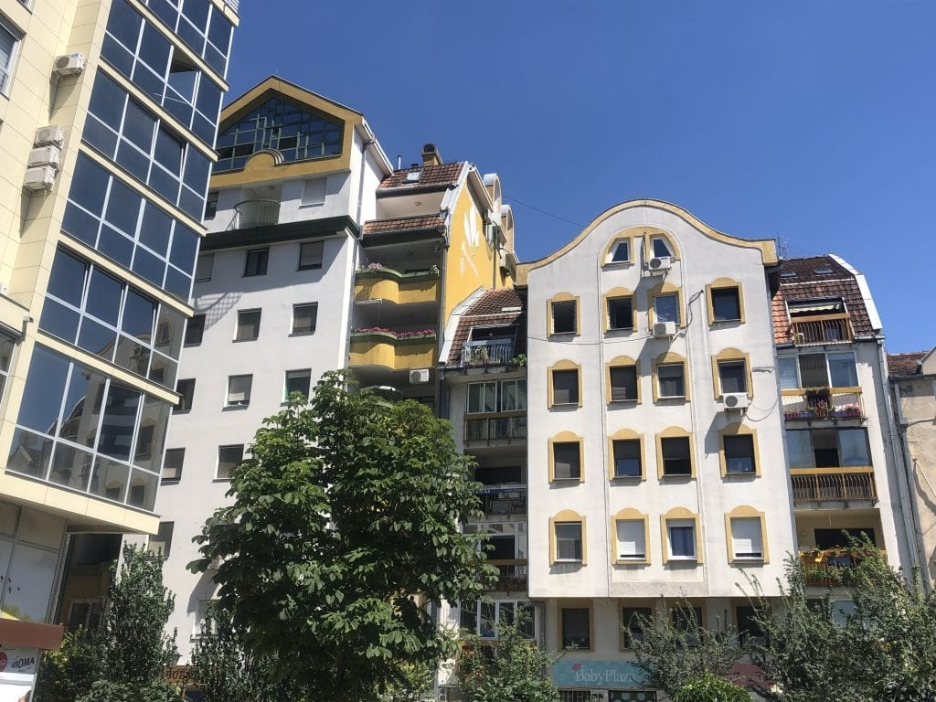 Bright white and yellow modern buildings stacked next to each other in Novi Sad, Serbia.