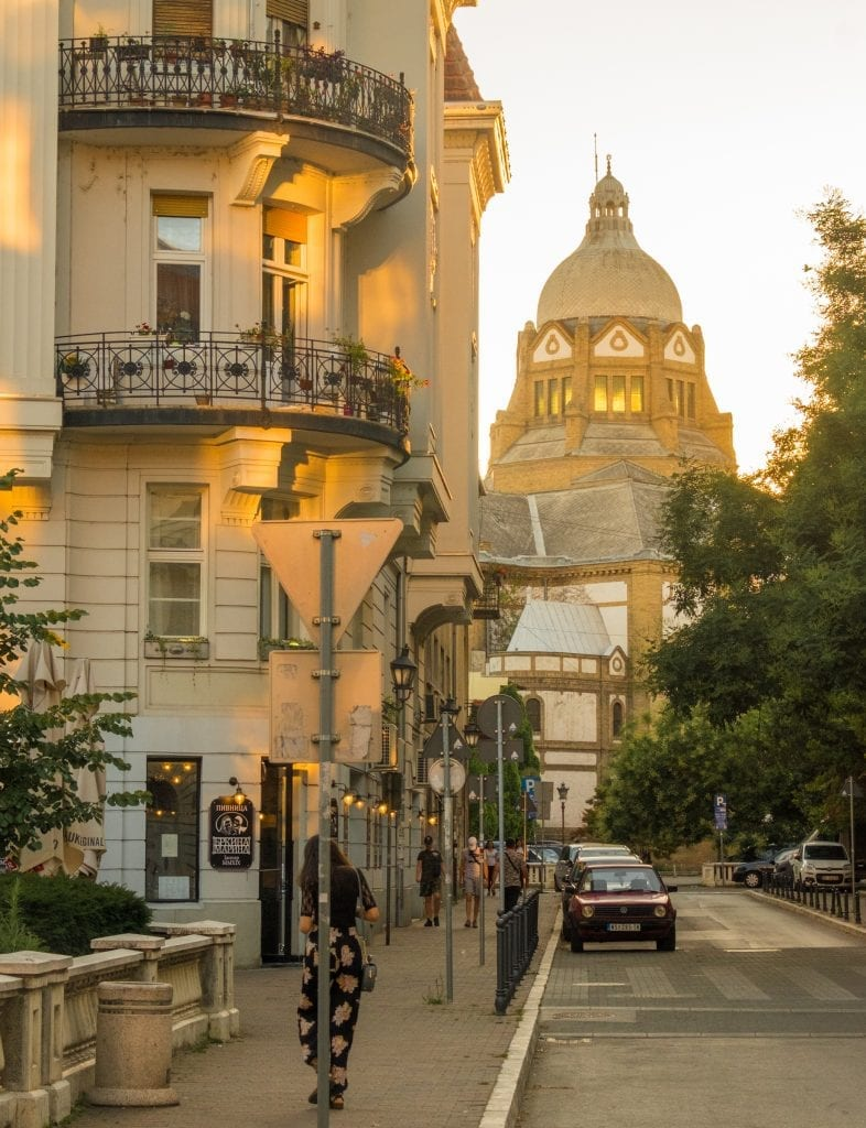 Novi Sad's synagogue lit up yellow at sunset, a woman leaning against a pole in the foreground.