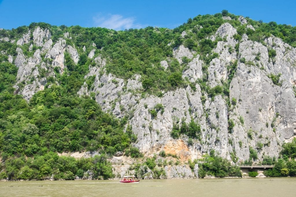 Tall limestone cliffs on the murky green Danube river, a tiny red speedboat showing you scale.