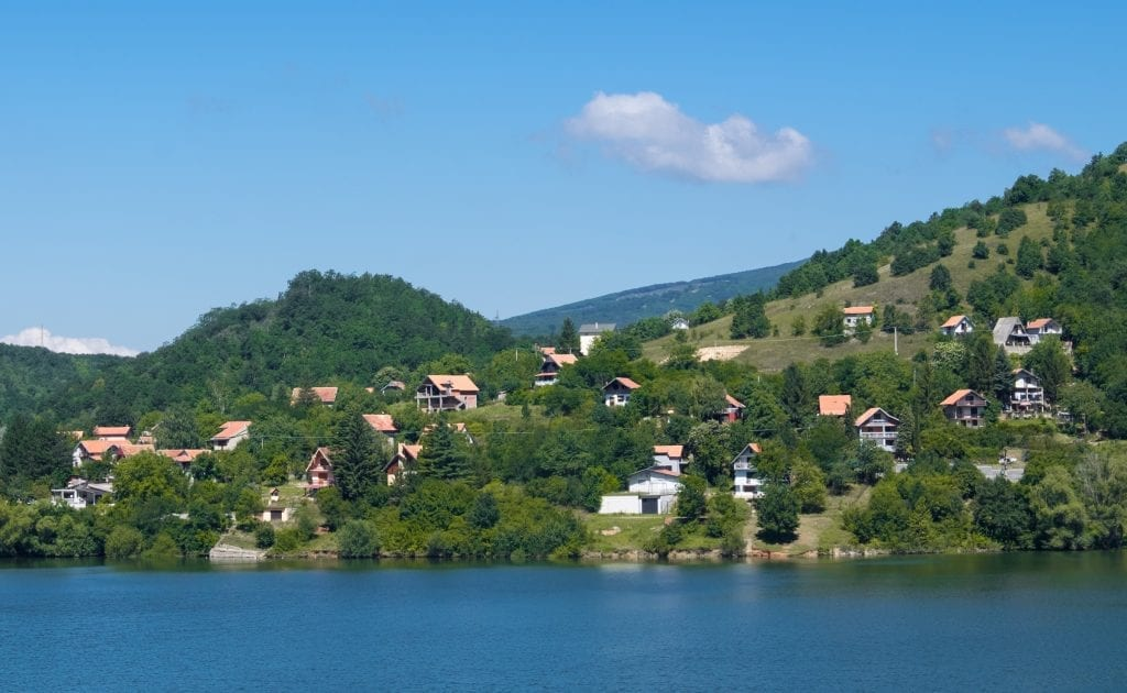 A bright blue lake in Serbia, white houses with orange roofs on the shore.