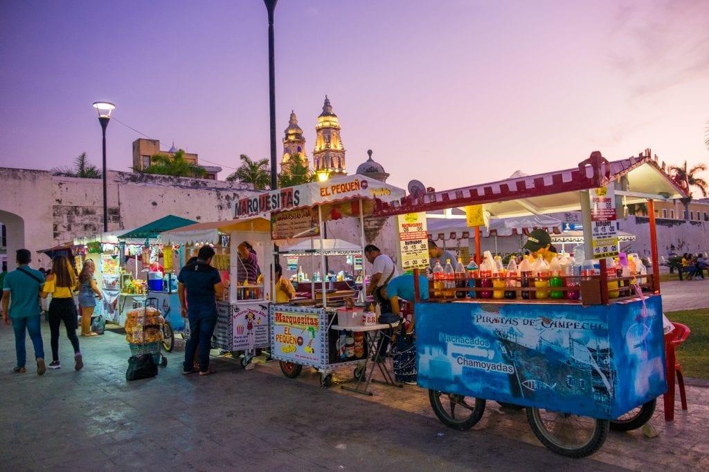 Street vendors serving food, set against a purple evening sky.