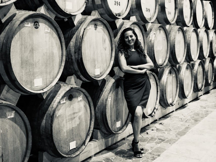 Kate stands in front of wooden bottles filled with brandy at the Ararat Distillery in Yerevan, Armenia.