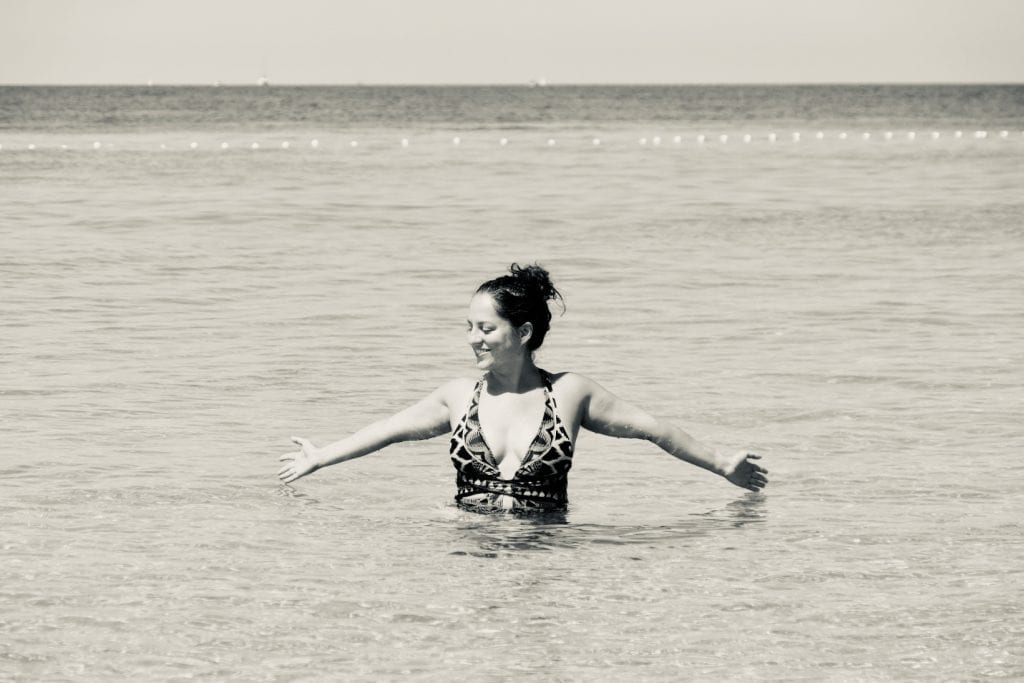 Kate stands in waist-deep water with her hands splayed, smiling and looking to the side, in Croatia.