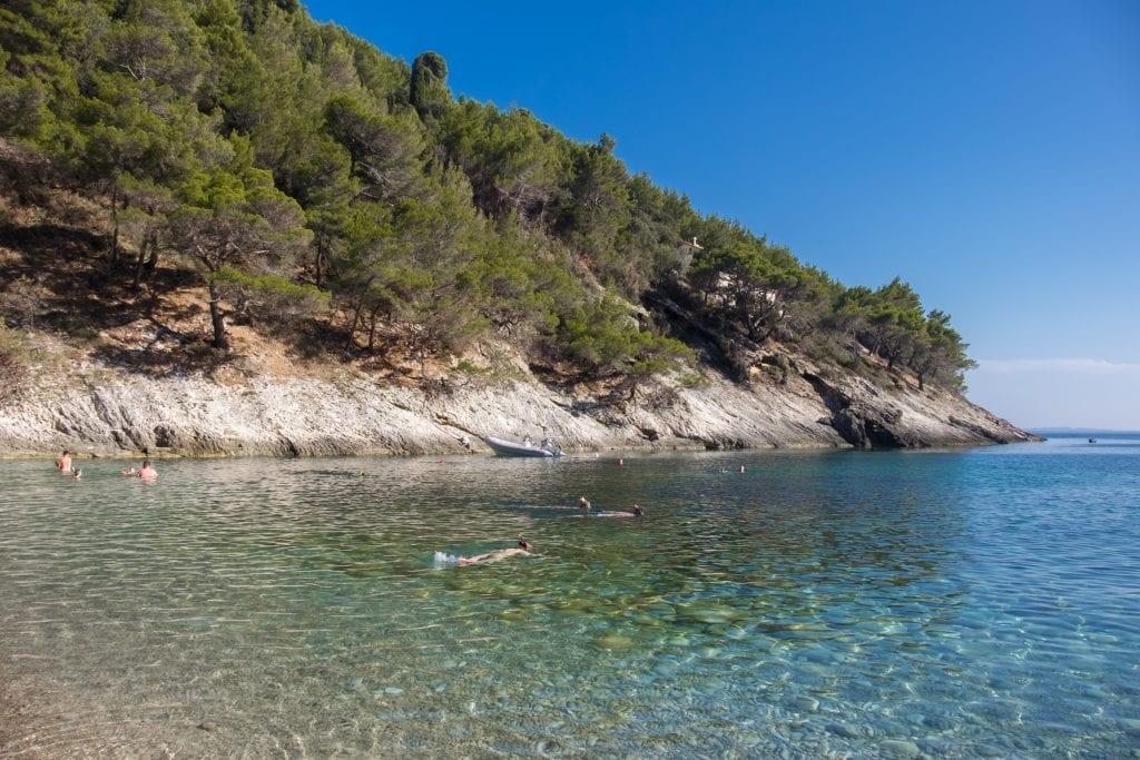 Bačva Beach: a few kids snorkeling in calm, clear blue-green water.