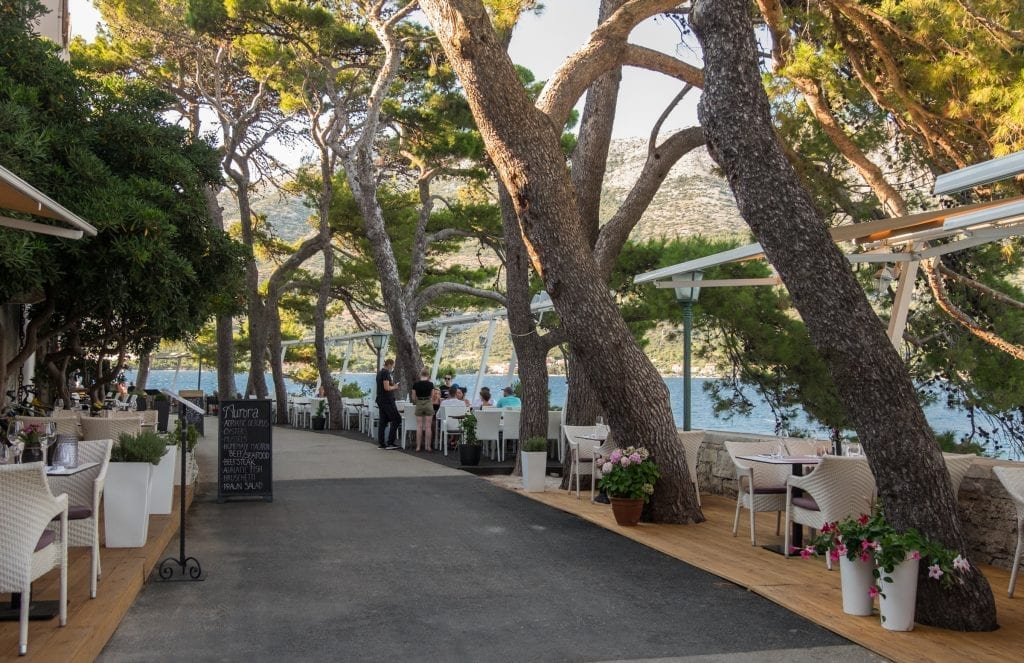The path around the old town, edged with trees, tables for dining, and the ocean and mainland in the background.