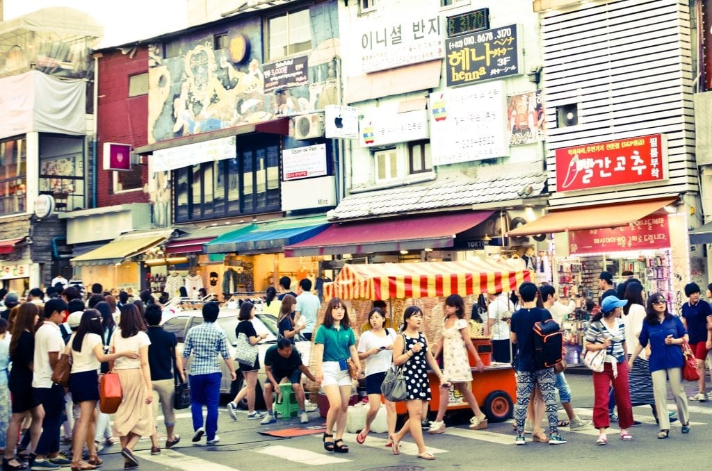 Women walking down the colorful street filled with signs and street vendors in Hongdae, Seoul.