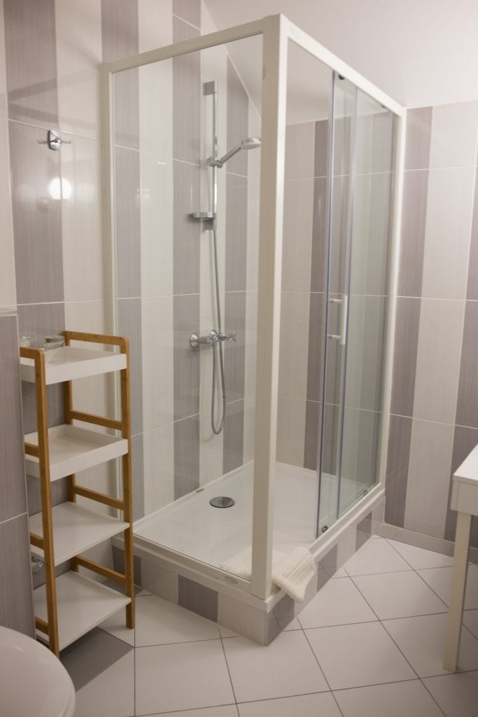 A modern bathroom with a clear glass shower in the hotel.