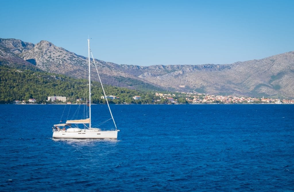 A sailboat in the navy blue water, mountains in the background.