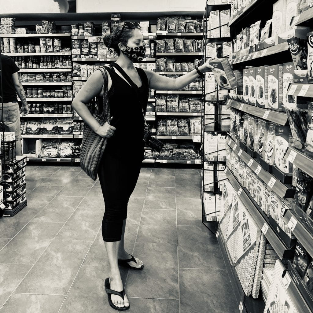Kate wears a mask and shops for groceries.