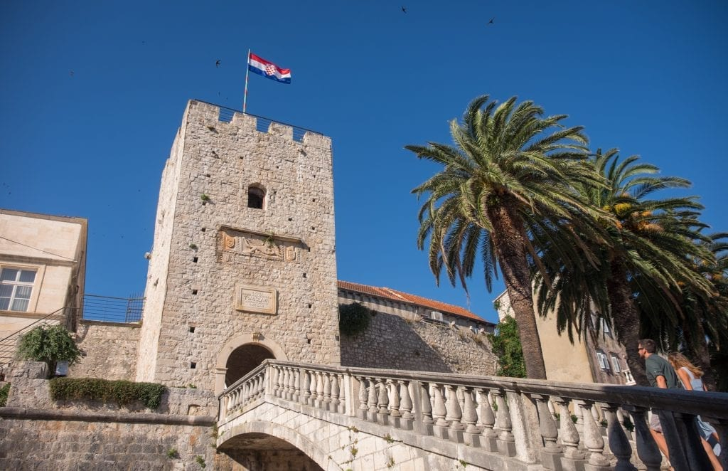 A stone staircase edged with palm trees leading to a tower in Korčula's Old Town.
