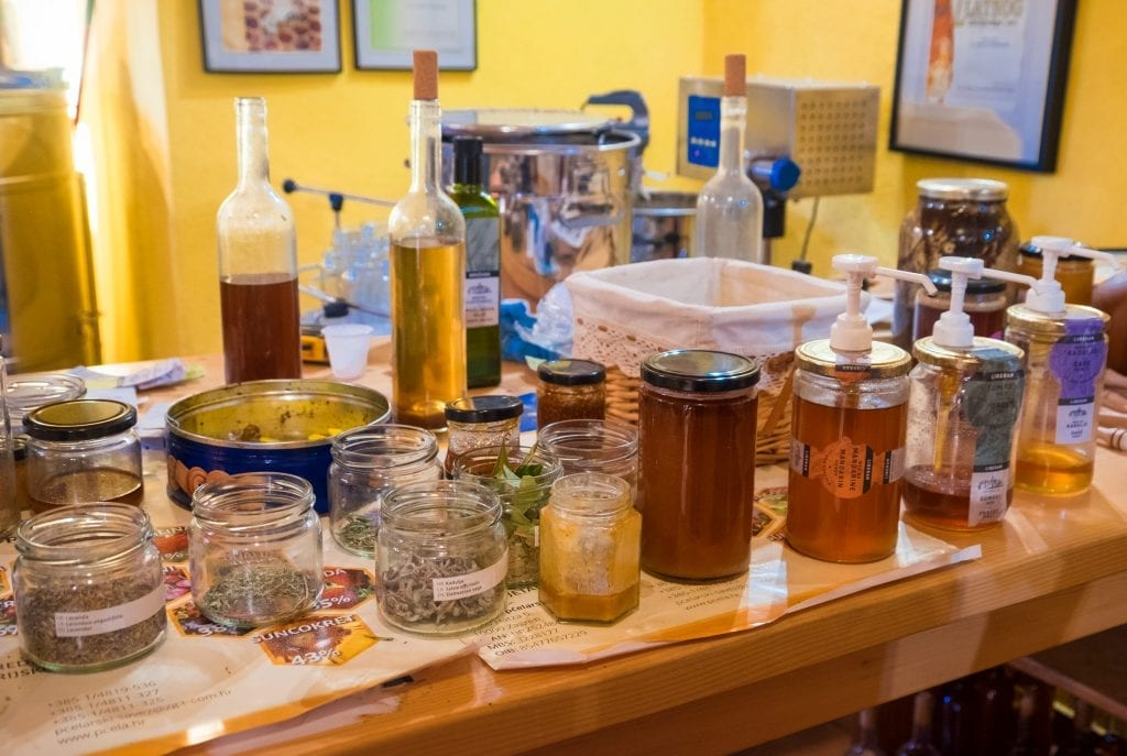 Stacks of herbs, honeys, and oils in a honey shop.