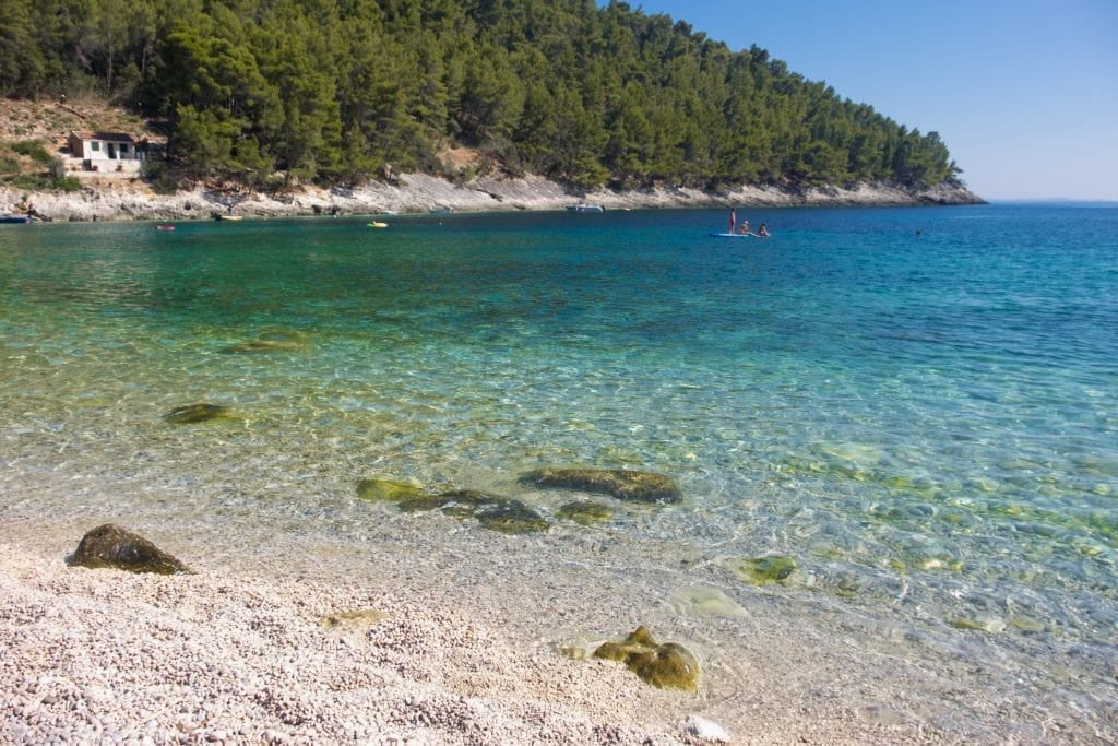 A pebbly beach with clear blue-green water, a few people on a stand up paddle board in the distance.