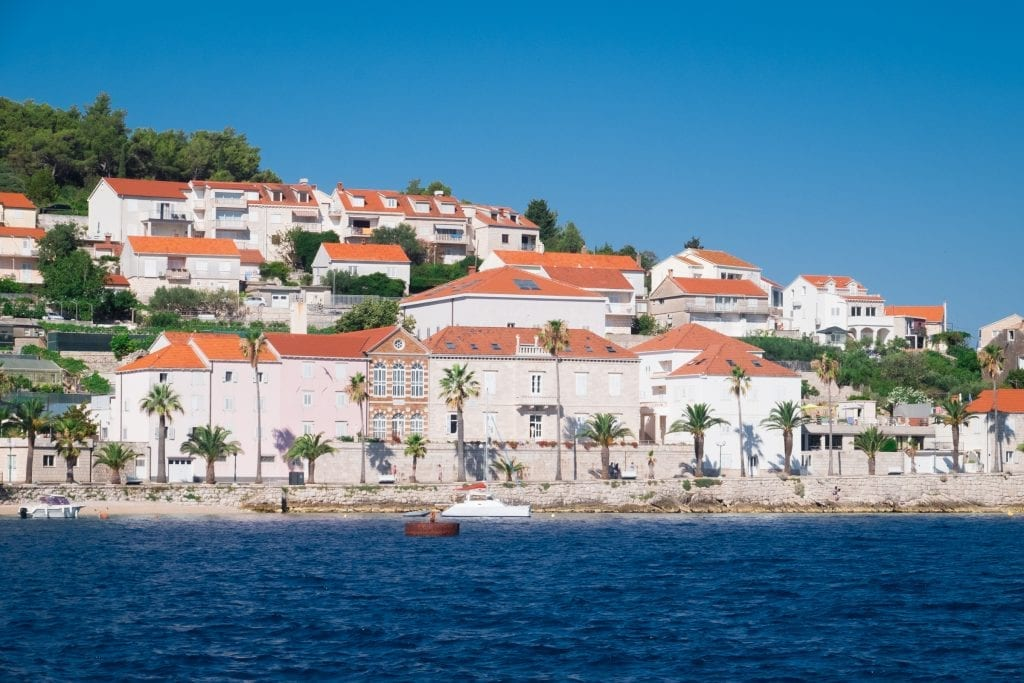 Korcula Town up close: rows of white houses with orange roofs on the edge of the navy blue ocean.