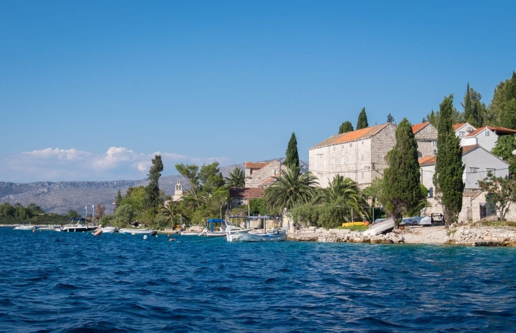 A close-up of Vrnik island with boats anchored to shore, stone buildings with terra cotta roofs, and lots of palm and cypress trees.