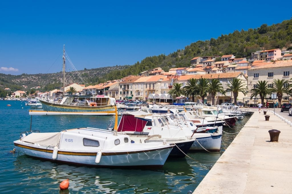 Vela Luka: a row of boats anchored to the waterfront, palm trees and orange-roofed houses in the background.