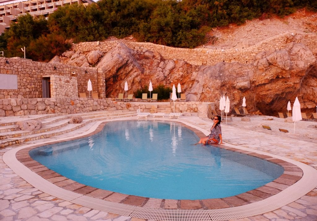 Kate sitting in a pool at the Hotel Dubrovnik Palace, filled with pink light. The pool is blue and wavy-edged, set amongst a rocky pink-orange setting.