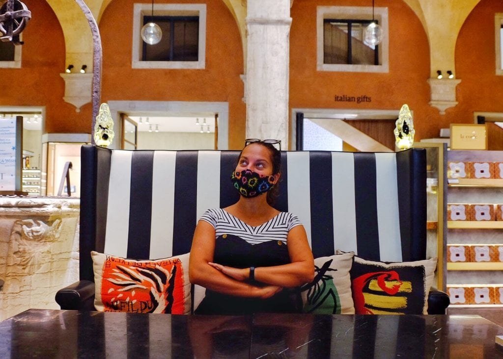 Kate sits on a black and white striped booth in a department store in Venice, columns behind her. She has her arms crossed and she's wearing a black face mask covered with splashes of color, and she's looking upward.