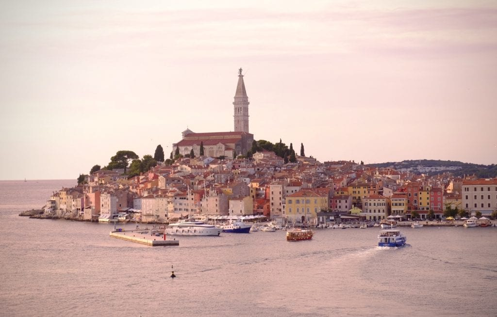 A pink-tinted image of Rovinj, looking like buildings on a peninsula with the church poking straight up on top, set in the water.